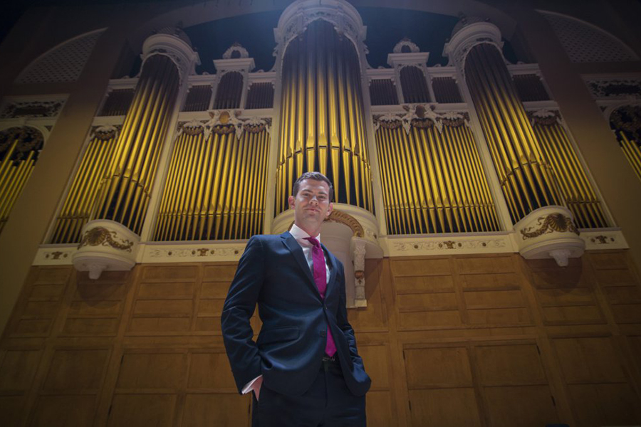 Organist James Kennerley poses in front of a large organ